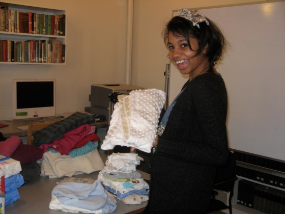 My high school feminism student, Ayana, organizes baby clothes to deliver to the children of GEMS girls in 2009 (photo credit: Ileana Jiménez).